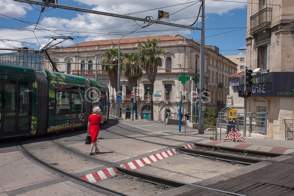 A  lady wearing a red dress walsk across the junction of rail tracks and roadways on the high overpass of the L1 and L3 tram routes at Gare Saint-Roch on 19th June 2016, in Montpellier, France. A tram operated by Transports de lAgglomeration de Montpellier TAM, a subsidiary of Transdev rumbles past, turning a corner and moving towards the next stop at the station. Montpellier has jumped from the countrys 25th to 8th largest city in the last 25 years and the landscape of transport infrastructure is part of 15.2km of tramways whose introduction is seen as a major contributor to the achievement of strict new EU standards on air quality.