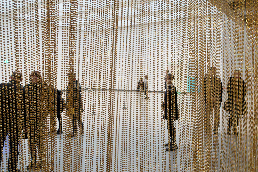 Visitors interacting with artworks at the Space Shifters exhibition at the Hayward Gallery on 16th December 2018 in London, United Kingdom. The exhibit was a major group show of sculptures and installations that explored perception and space, featuring 20 artists. Untitled golden by Felix Gonzales-Torres.