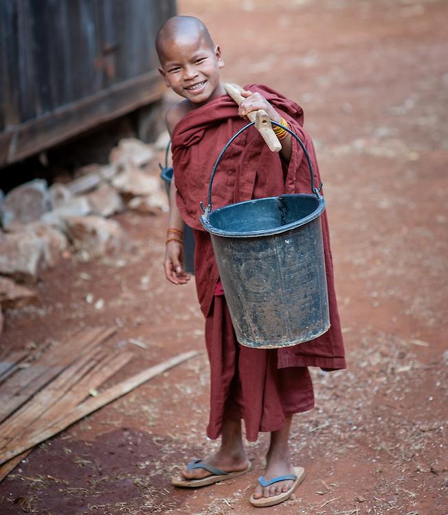 Novice Buddhist monk carrying a bucket of water (Myanmar)