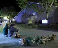 Augusta, New Jersey - Race organizers rest on the course at night as runners pass the race clock in the background during the 6-, 12-, 24- and 72-hour races during the 3 Days at the Fair races at Sussex County Fairgrounds on May 12, 2012.