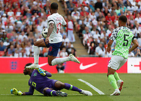 Football - 2018 International Friendly (pre-World Cup warm-up) - England vs. Nigeria<br /> <br /> Francis Uzoho (Nigeria) spreads himself to prevent Raheem Sterling (England) at Wembley Stadium.<br /> <br /> COLORSPORT/DANIEL BEARHAM