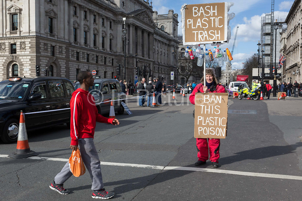 On the occasion of Commonwealth Day, a man carrying a plastic bag walks past an environmental activist standing in Parliament Square, advocating the ban on plastics around the world, on 11th March 2019, in Westminster, London, England.