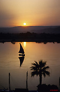 Felucca sails on the Nile River at sunset over West Thebes.