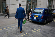 A tall man wearing a blue suit strides past a parked taxi in the same blue, in the City of London - the capitals financial district, on 4th June 2018, in London, England.