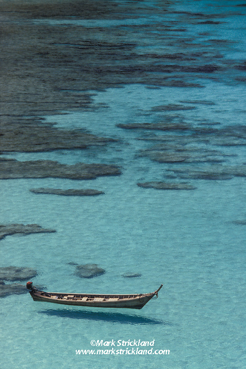 A traditional Thai Longtail Boat floats in clear, shallow waters. Similan Islands Marine National Park, Thailand, Andaman Sea
