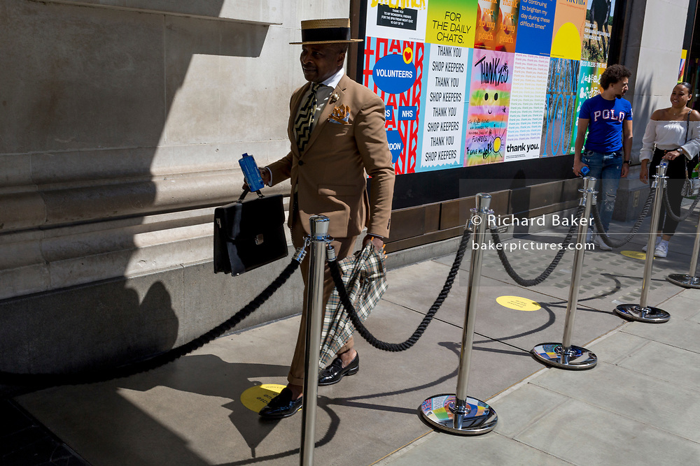 """In the 24hrs that a further 38 died from Coronavirus, bringing the total to 41,736, a further easing of the UK's Covid pandemic lockdown restrictions took place with many high street shops today being allowed to re-open after three months of forced closure. Prime Minister Boris Johnson, wanting to stimulate the economy, has urged people to """"shop with confidence"""" and long queues formed outside the main brands. But unlike on public transport, face coverings are not compulsory so shop floors and shopping practices have had to be adapted to ensure customers' social distances, amid fears of a second infection wave. A stylish man queues 2 metres apart from other shoppers outside Selfridges on Oxford Street, on 15th June 2020, in London, England."""