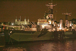 HMS Belfast night time view with Tower of London in background, River Thames, London