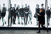 A pre-Christmas shopper walks past a video ad loop for theLondon retailer 'Reserved', on Oxford Street, on 22nd November 2017, in London England.