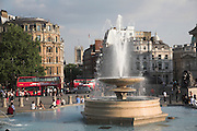 Fountain and passing red double decker buses, Trafalgar Square, London, England
