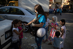 © Licensed to London News Pictures. 16/08/2020. Beirut, Lebanon. A worker from UNICEF hands out 1000LBP notes (also known as Lebanese Lira) to young children in the Karantina district of Beirut which has been badly destroyed following the huge explosion in Beirut Port on 4 August. Photo credit : Tom Nicholson/LNP