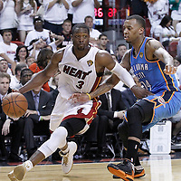 21 June 2012: Miami Heat shooting guard Dwyane Wade (3) drives past Oklahoma City Thunder shooting guard Daequan Cook (14) during the Miami Heat 121-106 victory over the Oklahoma City Thunder, in Game 5 of the 2012 NBA Finals, at the AmericanAirlinesArena, Miami, Florida, USA. The Miami Heat wins the series 4-1.