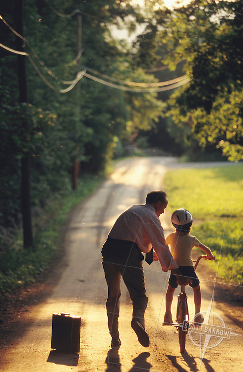Father giving his daughter a bicycle riding lesson on a sunlit country lane.