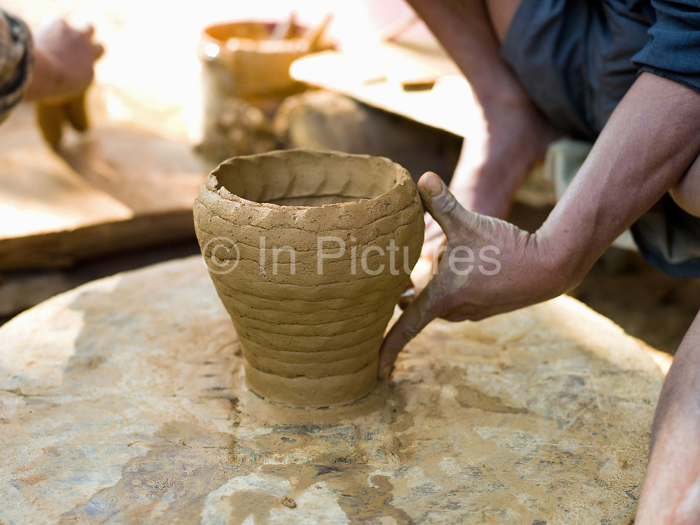 Making a ceramic pot using a wheel in the specialist pottery village of Ban Chan, 3 km from the heritage city of Luang Prabang, where age old traditions and methods continue to be used for producing pottery both for local use and commercial markets.