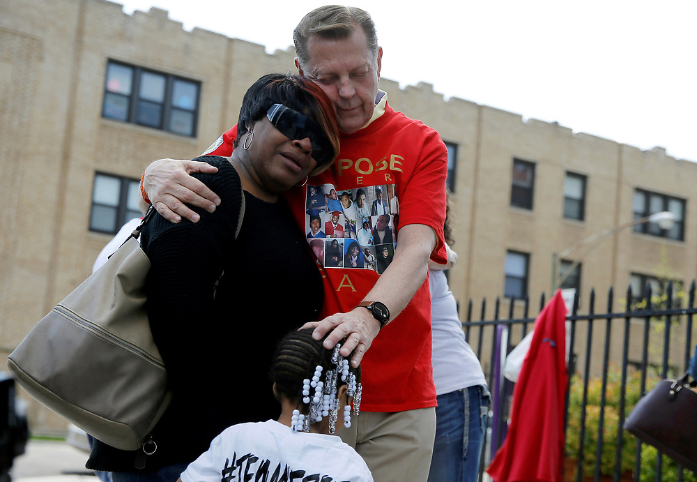 """Father Michael Pfleger (R) comforts Lutrice Boyd and her granddaughter Faith Davis during a news conference by """"Purpose over Pain"""", a group of mothers who lost children to gun violence, calling for a stop to shootings in Chicago, Illinois, United States, in this May 6, 2016 file photo.  REUTERS/Jim Young"""