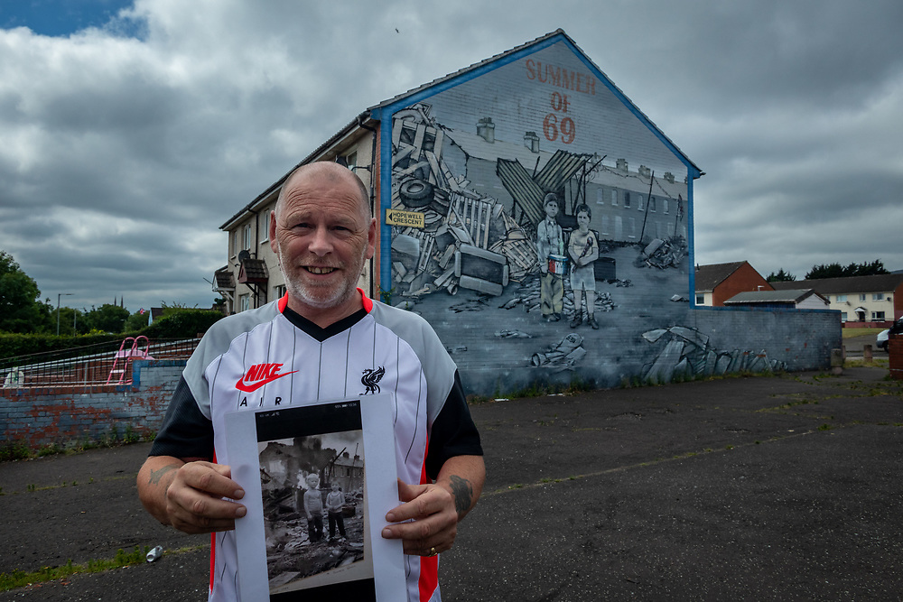Local resident holding the original photograph, stands in front of the Summer of 69 mural in protestant zone, Shankill estate. West Belfast.  Mural depicts the IRA bombings during the summer of 1969 and shows two boys standing in front of of their homes that have been destroyed.