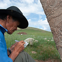 """Mongolian archaeologist Tovuudorj Sanjmyatov (""""Sasha"""") (MR) sketches carvings on a 2700+ year-old, bronze age deer stone monument at Ulaan Tolgai archaeological site near Lake Erkhel, north of Muren, Mongolia.  Sasha is a pioneer Mongolian researcher, who did much work and publication during the Soviet era.  <br /> MS0702_060626_0129.NEF"""