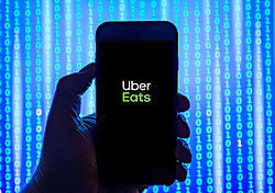Person holding smart phone with  Uber Eats food ordering and delivery service  logo displayed on the screen. EDITORIAL USE ONLY