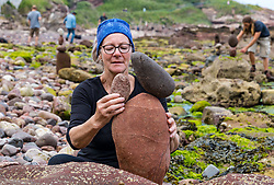 Dunbar, East Lothian, Scotland, United Kingdom 10 July 2021. European Stone Stacking Championship: The first day of the event, which is part of the Edinburgh Science Festival.  Pictured: Caroline Walker, from Edinburgh, specialises in finely balanced stones.<br /> Sally Anderson | EdinburghElitemedia.co.uk