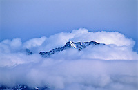 The tip of 14,037 ft. Little Bear Peak of the Sangre De Cristo Mountains.  The peak appears through the winter storm clouds.  Colorado.