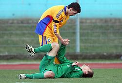 Razvan Ochirosii of Romania helps injured Armin Bacinovic (8)  of Slovenia during Friendly match between U-21 National teams of Slovenia and Romania, on February 11, 2009, in Nova Gorica, Slovenia. (Photo by Vid Ponikvar / Sportida)
