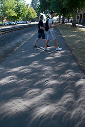 August 21, 2017 - Corvallis, Oregon, U.S - The partially eclipsed sun casts shadows on a side walk as people gather to watch the total solar eclipse as seen from the State University campus in Corvallis. (Credit Image: © Robin Loznak via ZUMA Wire)