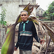 Portrait of an elderly Vietnamese man holding a leaf, That Vien, Hung Yen province, Vietnam