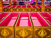 "29 MARCH 2017 - BANG KRUAI, NONTHABURI, THAILAND:  Rows of coffins after a ""Resurrection Ceremony"" at Wat Ta Kien (also spelled Wat Tahkian), a Buddhist temple in the suburbs of Bangkok. People go to the temple to participate in a ""Resurrection Ceremony."" Groups of people meet and pray with the temple's Buddhist monks. Then they lie in coffins, the monks pull a pink sheet over them, symbolizing their ritualistic death. The sheet is then pulled back, and people sit up in the coffin, symbolizing their ritualist rebirth. The ceremony is supposed to expunge bad karma and bad luck from a person's life and also get people used to the idea of the inevitability of death. Most times, one person lays in one coffin, but there is family sized coffin that can accommodate up to six people. The temple has been doing the resurrection ceremonies for about nine years.         PHOTO BY JACK KURTZ"