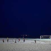 Young aspiring footballers play a game on Copacabana Beach during an evening workshop run by the Flamengo Football Club, Rio de Janeiro,  Brazil.  13th September 2010. Photo Tim Clayton.