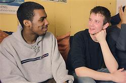 Two teenage boys sitting together talking,