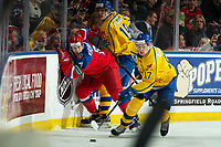 KELOWNA, BC - DECEMBER 18: Aleksandr Khovanov #7 of Team Russia is checked by Oskar Bäck #15 as Filip Sveningsson #17 of Team Sweden clears the puck from the corner during first period at Prospera Place on December 18, 2018 in Kelowna, Canada. (Photo by Marissa Baecker/Getty Images)***Local Caption***