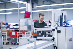 Young man working in books printing industry, Bremgarten, Hartheim am Rhein, Baden-W¸rttemberg, Germany