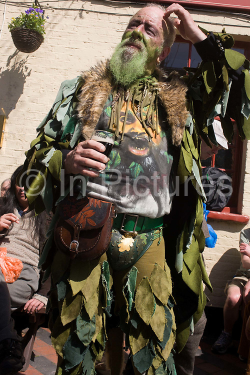 """Members of the Deptford Jack in the Green dance from pub to pub to Greenwich, London to mark the start of spring. In the 16th and 17th centuries in England, people would make garlands of flowers and leaves for the May Day celebration. After becoming a source of competition between works Guilds. Participants wear traditional green faces and forest foliage, at tradition from the 17th Century custom of milkmaids going out on May Day with the utensils of their trade decorated with garlands and piled into a pyramid which they carried on their heads. Amongst modern """"folkies"""" and neo-pagans the Jack in the Green has become identified with the mysterious Green Man depicted in mediaeval church carvings and is widely felt to be an embodiment of natural fertility, a spirit of the primeval greenwood and a trickster."""