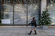 After a bleak year of Coronavirus pandemic misery, a shopper wearing a face mask walks past the temporary Christmas-themed Harvey Nichols window which urges Londoners to be optimistic for the coming year, on 13th November 2020, in London, England.