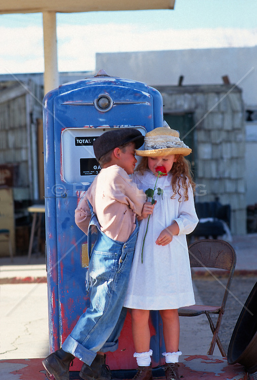 Young boy trying to kiss a girl standing next to a gas pump