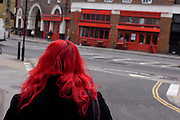 Seen from the rear, a red-haired woman walks towards a business with red as its theme of frontage in north London.