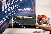 26 SEPTEMBER 2020 - DES MOINES, IOWA: A man attaches a Donald J. Trump flag to his truck before a pro-Trump motorcade. More than 1,500 people in 500 vehicles participated in motorcade through Des Moines Saturday. They started in the suburbs south of downtown, drove through downtown, and ended at the State Capitol.        PHOTO BY JACK KURTZ