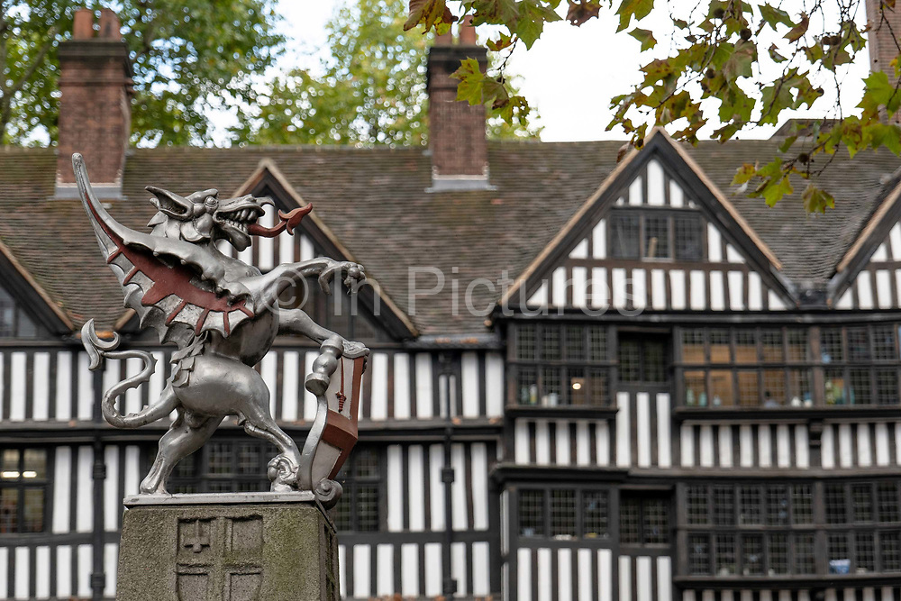 A small cast iron, silver painted dragon statue, holding a shield bearing the City of London coat of arms, in front of the part-Tudor Staple Inn building on the 27th September 2019 in London in the United Kingdom.