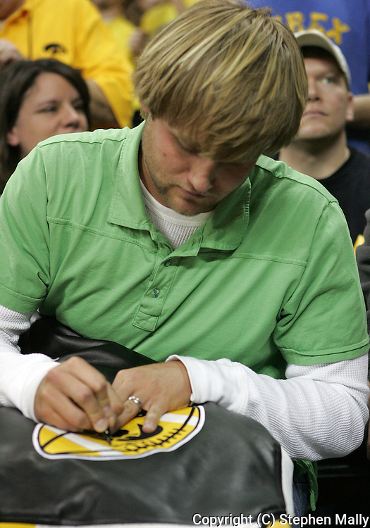 15 FEBRUARY 2007: Nate Kaeding (K - San Diego Chargers) autographs a coat for a fan during Iowa's 66-58 win over Northwestern at Carver-Hawkeye Arena in Iowa City, Iowa on February 15, 2007.