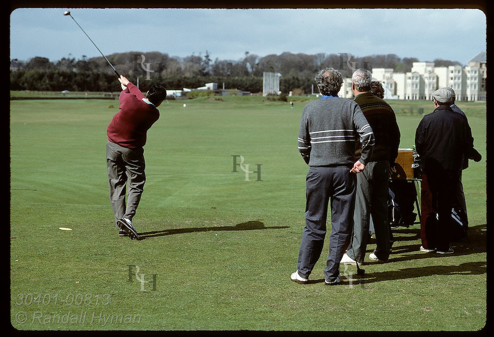 Friends watch as man tees off at the first hole of the famous Old Course at St. Andrews Links. Scotland