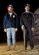 Two livestock farmers stand in their barn.