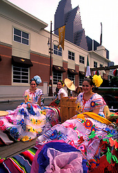 Stock photo of women in typical Mexican costumes sitting on parade float during the Cinco de Mayo parade in downtown Houston Texas