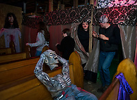 Not your ordinary day in church for this group hearing the confessions of the dead during their visit to the Haunted House in Hill.  (Karen Bobotas/for the Laconia Daily Sun)