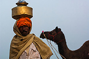 Rajusthani pastoralist fetching water and preparing for the day at the Pushkar camel and livestock fair which takes place in the Hindu month of Kartik (October / November) ten days after Diwali (Festival of Lights). Pushkar has always been the the region's main market for herdsman and farmers buying and selling camels, horses, indigenous breeds of cattle and even elephants. Over the years this annual trading event has increased in volume to become one of the largest in Asia. Temporary tents and campsites suddenly appear to accomodate the thousands of pilgrims, villagers and tourists. Entertainers and contests abound and a festive funfair atmosphere prevails over Pushkar during the Mela's 2 week duration. Thousands of men come first with their camels, horses and cattle and camp on the dunes to transact business. 3 days before the full moon the women arrive beautifully attired. The town of Pushkar is one of the holiest centers of Hinduism and houses one of the few Brahma Temples in India. It is one of the 5 essential pilgrimage centers which a Hindu must visit in his lifetime along with Badrinath, Puri, Rameshwaram and Dwarka. The 12 day fair culminates in a religious Hindu pilgrimage and reaches a crescendo on the night of the full moon (Purnima) when pilgrims take a dip in the holy lake.  <br /> Pushkar, Rajasthan. INDIA