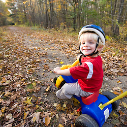 A young boy (age 2) on his  bike.  Newfields rail trail in Newfields, NH.  Fall. MR