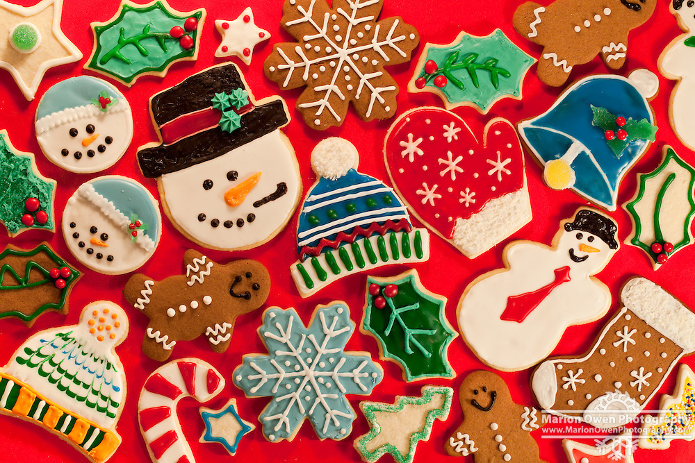 Colorful homemade Christmas cookies arranged on a red tablecloth.