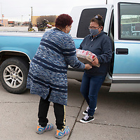 Mona Fraiser, left, receives a case of pork and beans donated by Betsy Begay at St. Paul Missionary Baptist Church Monday during their food drive benefiting the Community Pantry in Gallup. Fraiser organized the food drive in honor of Dr. Martin Luther King Jr. day in place of their annual celebration due to COVID-19 restrictions.