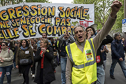 April 27, 2019 - Paris, France - A demonstrator in a Yellow Vest raises his fist in the air in front of a large Social Front banner during the march reached Place d'Italie from Montparnasse Station. (Credit Image: © Samuel Boivin/NurPhoto via ZUMA Press)