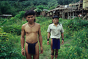 Twenty three years ago: Baru and Banai Tebai standing in front of a temporary 'sulap' structure, made from a mixture of timber, bamboo and rattan. Semi-nomadic Penan, indigenous hunter-gatherers, dressed in traditional 'chawats' loincloth. Long Tegang, Limbang district, Sarawak, Borneo 1989<br /> <br /> Semi-Nomadic Penan, MALAYSIA. Sarawak, Borneo, South East Asia.Penan men with their sulap settlement  . Tropical rainforest and one of the world's richest, oldest eco-systems, flora and fauna, under threat from development, logging and deforestation. Home to indigenous Dayak native tribal peoples, farming by slash and burn cultivation, fishing and hunting wild boar. Home to the Penan, traditional nomadic hunter-gatherers, of whom only one thousand survive, eating roots, and hunting wild animals with blowpipes. Animists, Christians, they still practice traditional medicine from herbs and plants. Native people have mounted protests and blockades against logging concessions, many have been arrested and imprisoned.