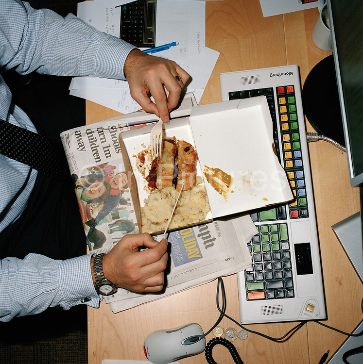 Working lunch in the office of a city firm. With the recession still responsible for rising unemployment workers have to be seen to be working hard. From the series Desk Job, a project which explores globalisation through office life around the World.