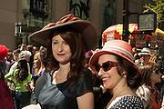Two women wearing hats that harken to the 1940s.